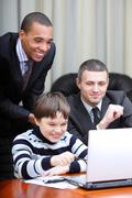 kid boy explains multi ethnic business team how to work - stock photo