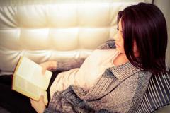 woman in casual cloths reading a book at home - stock photo