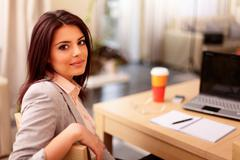 young businesswoman sitting at desk and working. smiling and looking back at  - stock photo