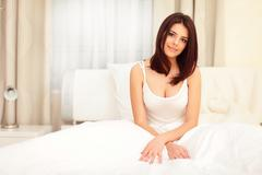 Very beautiful young woman sitting on the bed in the morning Stock Photos