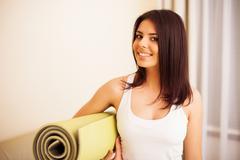 Nuori onnellinen nainen joogamatto on valmis fitness Kuvituskuvat