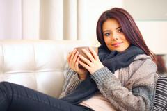 happy young woman sitting on sofa in cosy cloths with cup of coffee - stock photo