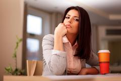 pensive young beautiful businesswoman sitting at desk - stock photo