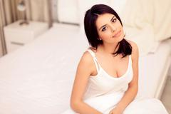 young beautiful serene woman sitting on the bed at home - stock photo