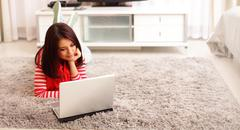 portrait of dreamy smiling young woman using laptop while lying on floor at h - stock photo