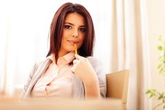 portrait of a young beautiful confident woman in casual business cloths holdi - stock photo