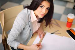 beautiful young architect with technical drawings - stock photo