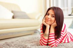 smiling teen girl in colorful cloths lying on floor and relaxing - stock photo
