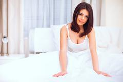 very beautiful young woman sitting on the bed in the morning - stock photo