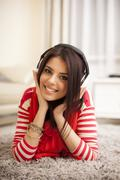 Young beautiful woman in bright outfit enjoying the music at home Stock Photos