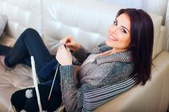 young woman knitting a scarf and smiling - stock photo
