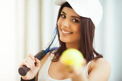 Healthy happy woman poses with a tennis racket while holding tennis ball Stock Photos