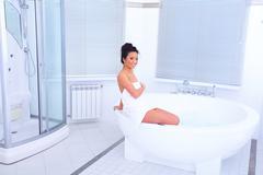 young beautiful asian woman sitting in modern bathroom with jakuzzi - stock photo