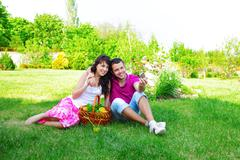 young couple taking photo of themselves on a picnic outdoors - stock photo