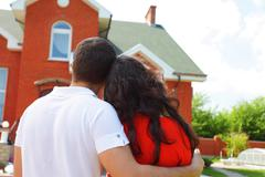 Happy couple in love in front of their home outdoors Stock Photos