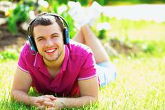 portrait of a young man listening to music lying on the grass - stock photo