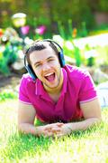 portrait of a young man listening to music outdoors and shouting - stock photo