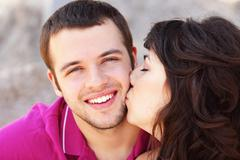 Young woman kissing her boyfriend in cheek Stock Photos