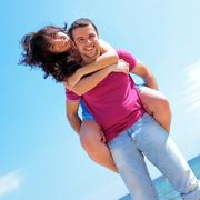Happy young couple in casual cloths at the beach in sunny weather Stock Photos