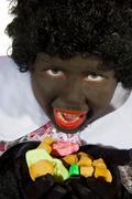 black piet is eating pepernoten - stock photo