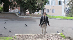 Happy young businessman playing with doves in the city street Stock Footage