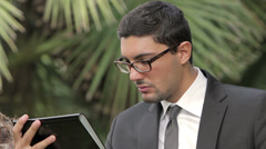 Business man using a digital tablet device while standing in a tropical zone Stock Footage