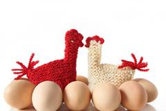 Egg Warmers in shape of knitted kissing hens Stock Photos