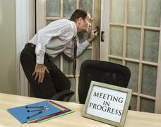 Man peeking into meeting in progress Stock Photos