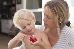 Mother and daughter with yoyo outdoors - stock photo