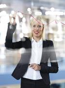 Portrait of business woman drawing red line on glass panel Stock Photos