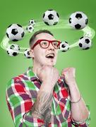 Young man with flying footballs around his head, Composite - stock photo