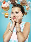 Young woman with flying cupcakes around her head, Composite - stock photo
