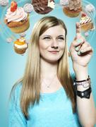 Teenage girl with flying cupcakes around her head, Composite - stock photo