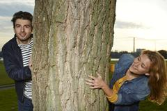 Germany, Dusseldorf, Young couple playing hide and seek Stock Photos