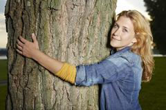 Stock Photo of Germany, Dusseldorf, Young woman hugging tree