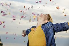 Stock Photo of Germany, Dusseldorf, Young cGermany, Dusseldorf, Young woman throwing petals