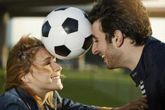 Germany, Dusseldorf, Young couple playing football Stock Photos