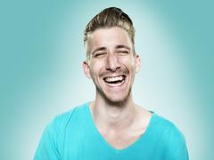Stock Photo of Portrait of laughing young man, studio shot