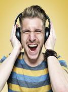 Portrait of screaming young man with headphones, studio shot - stock photo