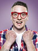 Stock Photo of Portrait of happy young man with red glasses, studio shot