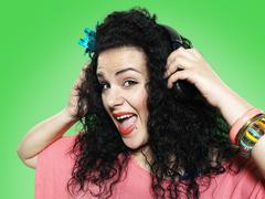 Portrait of young woman hearing music with headphones, studio shot Stock Photos