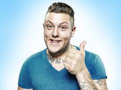 Portrait of happy young man with thump up, studio shot - stock photo