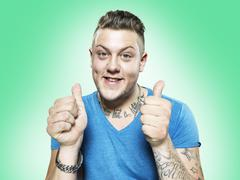 Portrait of happy young man with thumps up, studio shot - stock photo
