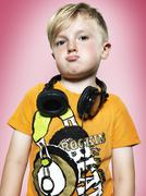 Portrait of pouting little boy with headphones, studio shot Stock Photos