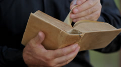 Catholic priest holding the bible Stock Footage