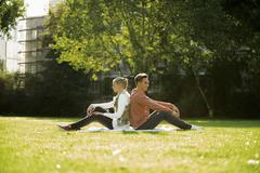 Young couple sitting back to back on a meadow - stock photo