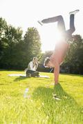 Young man doing a handstand on a meadow - stock photo