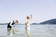 Stock Photo of Germany, Bavaria, Tegernsee, Wedding couple standing in lake, bride holding