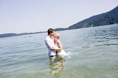 Germany, Bavaria, Tegernsee, Wedding couple standing in lake, kissing Stock Photos