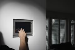 Germany, Cologne, Woman using tele control for roller blinds Stock Photos